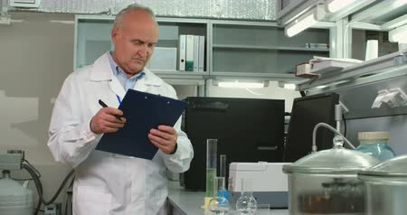 laboratorní plášť : Mature chemist working on his research in modern laboratory Dostupné videozáznamy