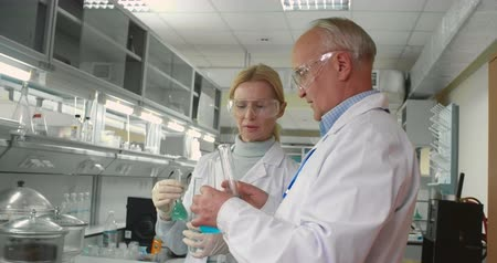 laboratórium : Two mature scientists working together with chemicals in lab