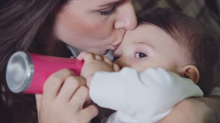 čelo : Young mother smooching forehead of her little son while he is drinking milk from baby bottle Dostupné videozáznamy