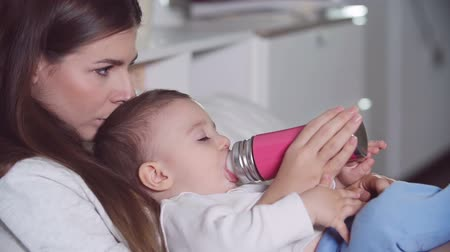 infant formula : Mom holding cute little boy in her arms and feeding him from baby bottle