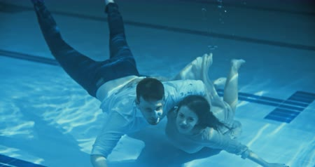 namorado : Smiling couple swimming underwater towards the camera and waving