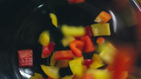 fresh food : Close-up of bell pepper pieces falling in glass bowl