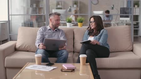 üzleti öltöny : Man and woman sitting in comfortable modern office and chatting Stock mozgókép