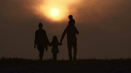 transportar : Family walking together towards sunset: little girl holding parents hands, dad carrying son on his shoulders