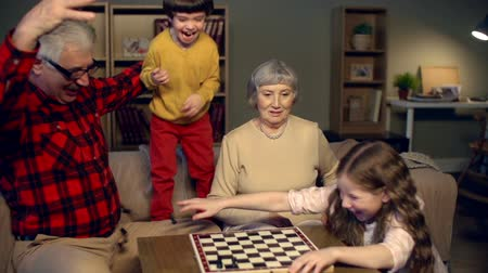 destruct : Naughty kids strewing chess pieces while playing chess with grandparents Stock Footage