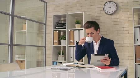 confiança : Confident business woman drinking coffee and checking email at office Vídeos