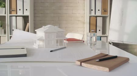 bina : Panning shot of 3d house model and plan placed on table in meeting room