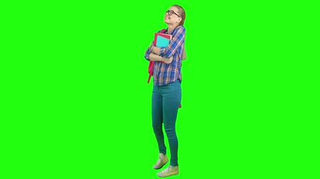 chroma key background : Beautiful blonde girl with backpack holding books, dancing and smiling on chroma key background