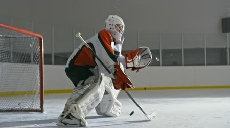hockey rink : Hockey goaltender standing with stick and catching pucks in front of the net Stock Footage