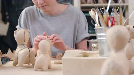 zanaat : Tracking shot of young female artistmaking papier-mache dog figures of craft paper Stok Video