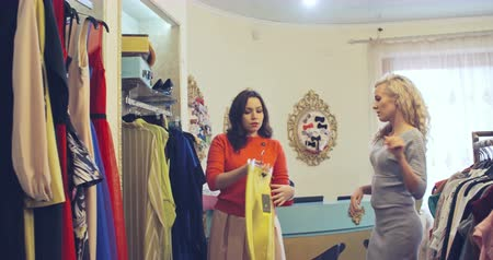 butik : Two pretty young ladies shopping together in clothes boutique: one girl holding hanger with yellow pants and showing them to her friend Stok Video