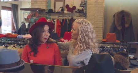 butik : Two beautiful ladies having fun while trying on wool fedora in fashion boutique