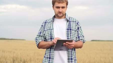 cultivo : Young farmer standing in the field with tablet, looking at camera and smiling