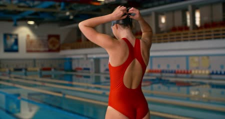 čepice : Rear view of sportswoman fixing her goggles, diving off from starting block and swimming in the pool