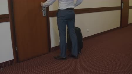 отель : Businessman with luggage walking to his room in hotel, opening the door and entering Стоковые видеозаписи