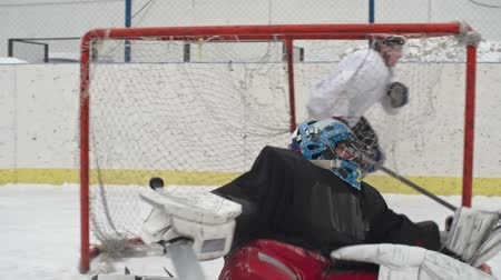 tiro : Ice hockey goalie failing to stop a shot and being scored in play at outdoor rink Stock Footage