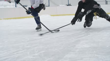 sporty zimowe : Hockey defenseman falling down on ice while knocking the puck off the stick of a puck carrier during a practice at outdoor rink
