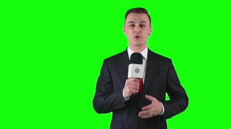 novinář : TV journalist standing on green screen background with microphone and talking
