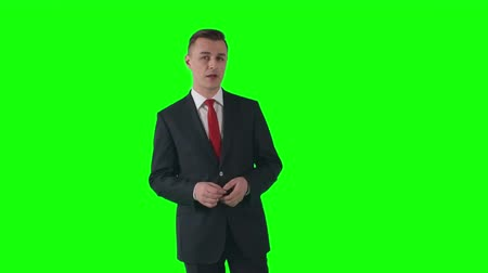 speaking : Young TV reporter in suit telling about latest news during his broadcast on green screen background
