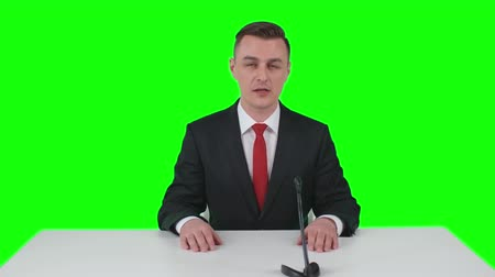 news tv : Newsman sitting in studio at the desk with microphone and telling some information on green screen background