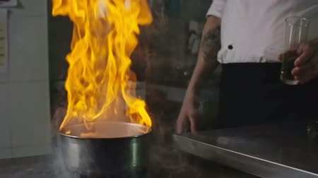 gastronomi : Close up of restaurant chef adding alcohol to a hot saucepan and creating a burst of flame in it to make a flambe dish