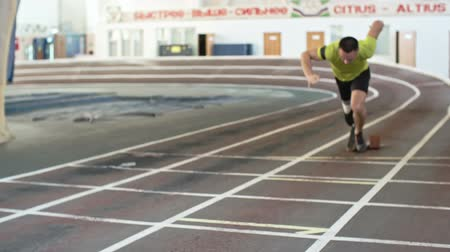 paralympic : Determined runner with prosthetic leg starting from blockson track