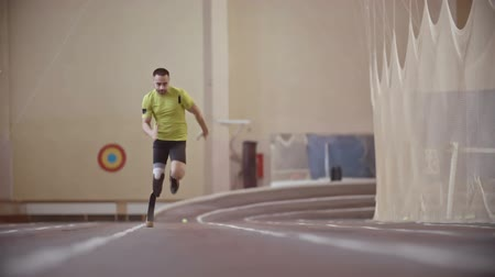 fogyatékosság : Determined Paralympic athlete with prosthetic leg running a racetowards the camerain slow motion Stock mozgókép