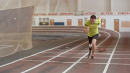 atleta : Determined amputee athlete with prosthetic leg starting from blocks and running in slow motion at indoor stadium Stock Footage