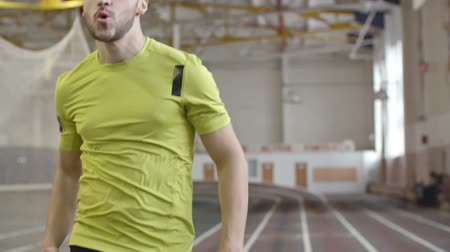 atlet : Dolly shot of determined amputee athlete with artificial leg running on trackat indoor stadium in slow motion Stok Video