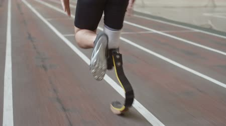 atleta : Follow shot of Paralympicamputee athlete with prosthetic leg running on trackin slow motion, rear view, tilt up