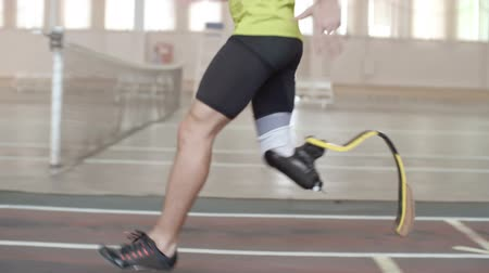 prosthesis : Tracking shot tilt-up of determinedParalympic athlete with prosthetic leg running on trackin slow motion