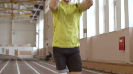 инвалидность : Tilt down of handsomeamputee athlete withprosthetic leg doing jumping exercise on trackat indoor stadium