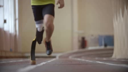 atleta : Paralympic athlete with prosthetic leg running on tracktowards the camerain slow motion