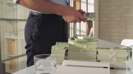 throwing in : Man standing in the architect office, counting stacks of money and throwing them on the table