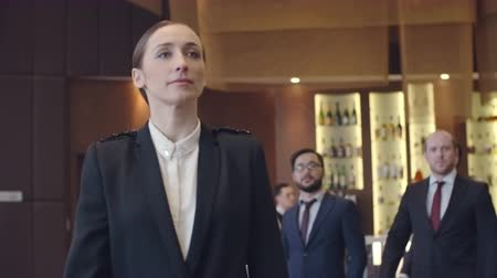 отель : Businesswoman walking in front of her male colleagues in the hotel restaurant