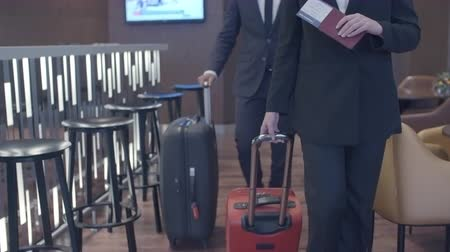 oblek : Tilt up of businesswoman and businessman walking with suitcases in hotel lobby