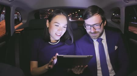 ülés : Businesswoman showing something on her tablet to her male colleague while sitting in the backseat of taxi cab, they talking and laughing Stock mozgókép