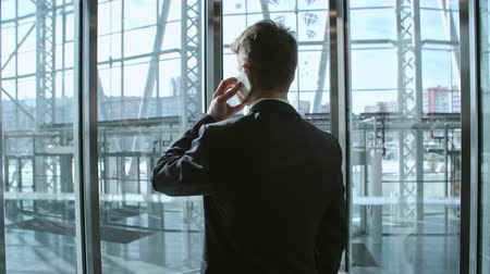 asansör : Rear view of businessman standing in modern glass elevator and talking on the phone