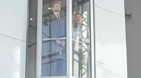 лифт : Low angle view of man and woman going up in the glass lift in business center Стоковые видеозаписи
