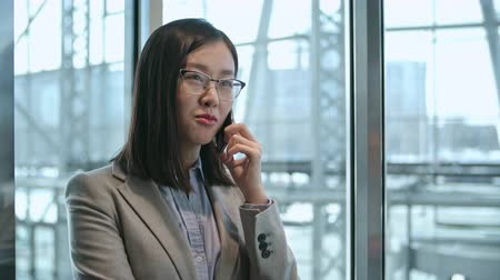 лифт : Young Asian businesswoman standing in the moving elevator and talking on the cell phone Стоковые видеозаписи