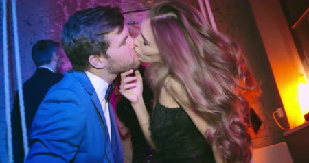 csókolózás : Beautiful young man and woman kissing at the party while their friends dancing behind them Stock mozgókép