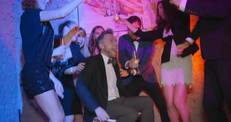 šampaňské : Company of friends dancing, drinking champagne and spinning man sitting on office chair at the party Dostupné videozáznamy