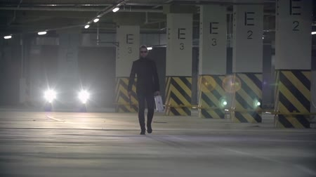 oblek : Gangster man in black suit and sunglasses with baseball bat and briefcase walking towards the camera in underground parking