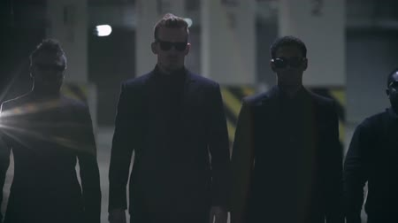 hooligan : Four gangsters in black suits and sunglasses walking towards the camera in slow motion