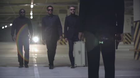 гангстер : Three criminals walking in slow motion in the underground parking to gangster standing with metal briefcase and handgun and waiting for them