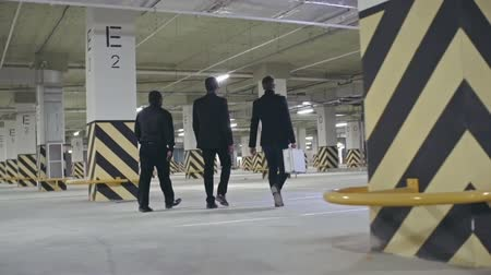 насилие : Rear view of three bandits walking in the underground parking; one of them holding metal briefcase and another man carrying baseball bat