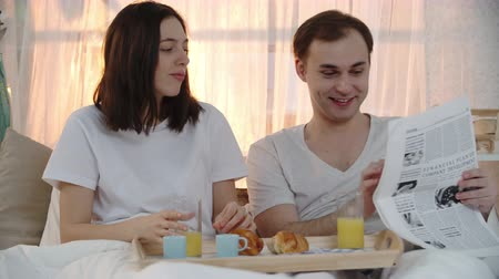 home life : Young couple spending their morning in bed: woman drinking orange juice and eating croissant while man reading hilarious article in newspaper, showing it to his wife and they laughing together Stock Footage