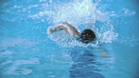 přední : Professional sportswoman swimming front crawl in pool in slow motion towards the camera