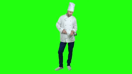 uniforme : Chef man in white uniform and hat standing on green screen background, looking down and holding ladle. In the end of video he tilting up his head and smiling at camera