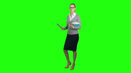 profesor : Serious young woman teacher standing on green screen background, holding books and ruler and looking at camera